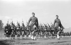 Men in kilts marching in formation with rifles and swords during celebration of Golden Jubilee at...