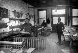 Interior of tinsmiths workshop with the proprietor, Magloire Desrosiers and his assistants