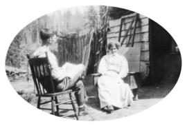 Adella Barwis Dorais sitting in a cedar chair made from the cedar log, with her son Lewis making ...