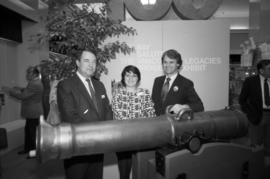 Unidentified man and woman with Gordon Campbell beside canon at Legacies event at The Bay