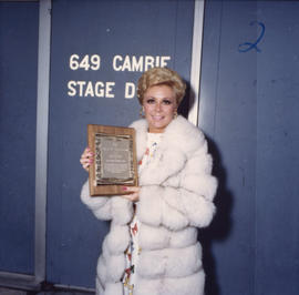 Mitzi Gaynor holding a plaque