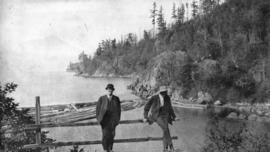 [Two men near forested shore]