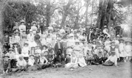 [Men, women and children assembled in clearing for picnic]