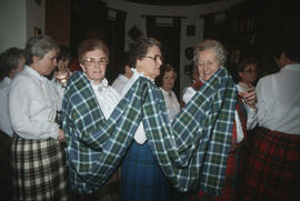 Group of women wearing kilts holding a piece of the Centennial tartan fabric