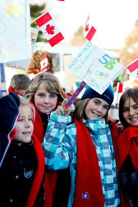 Day 25 Girls wave their Olympic signs in Shediac, New Brunswick's Community Celebration.