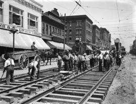 [Men laying streetcar tracks at Granville and Robson Streets, for reconstruction of Granville Str...