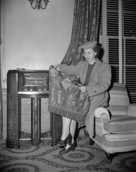 [Woman holding a shawl seated on the arm of a chair by a radio]