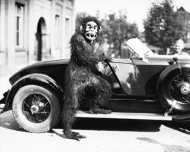 [Person in gorilla/monster costume standing beside luxury sports model car (Auburn?)]