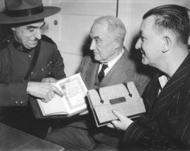 "[Corporal M.J. Olsen, Major J.S. Matthews and Thomas Howarth study copies of ""The Northwest ..."