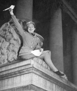 [A member of the Canadian Womens Army Corps seated on a courthouse lion celebrates the end of the...