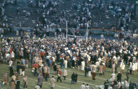 [Fans crowded on football field at 1958 Grey Cup game]