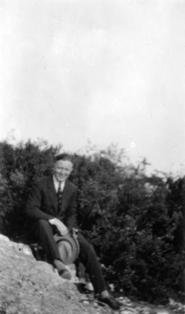 [George Fitch sitting on rocky hill]