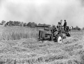 [Tractor pulling harvester]