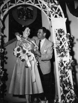 Man presenting sash to winner of Miss Vancouver pageant