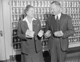 Mrs. Lillico [and an unidentified man beside shelves of tea at] Empire Tea Bureau