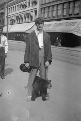 [Young man with bear cub on Hastings Street]