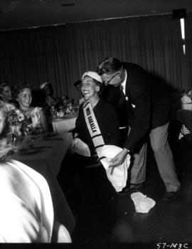 P.N.E. director T.A. Steeves presents unidentified woman with Miss Oakalla sash at tea party