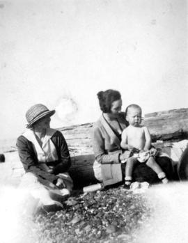 [Two women and small child sitting on beach at Summit Lake]