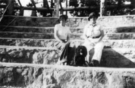 [Octavia Beaton and unidentified woman sitting on large stone stairs with dog]