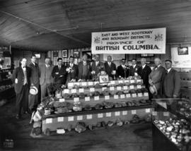 Group standing behind mineral display from East and West Kootenay and Boundary Districts