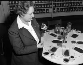 Mrs. Lillico [examining tea leaves at] Empire Tea Bureau