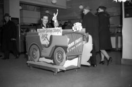 [Store clerk sitting in jeep shaped booth for selling war stamps inside the Woodward's store]