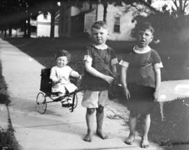 [Two boys pulling a toddler in a push cart]