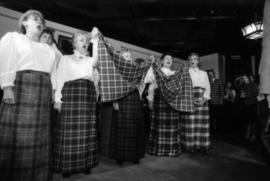 Group of women wearing tartan skirts singing and holding a piece of the Centennial tartan fabric