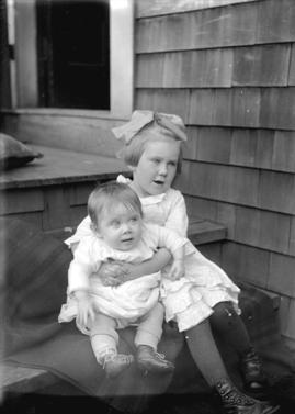 [Young girl holding baby sitting on steps of a house]