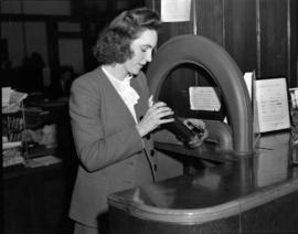 [Woman using the pneumatic tube delivery system at the Kelly Douglas Co., Ltd. offices]