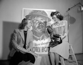 Miss Joan Feast and Miss Betty Jean Horne [in front of Victory Bond poster]