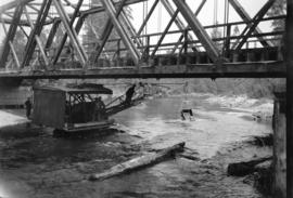[Grader under a bridge on the Fraser River]
