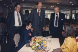 [Ted Allan], Mike Harcourt and unidentified man speaking with two women seated at table
