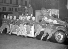 Football team pushing a Victory Bond parade float depicting Hitler, Stalin, and Hirohito