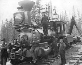 [Group of men with railway engine pulling logs]