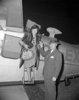 [Portrait of Mr. and Mrs. Whiteford leaving a plane at the airport]