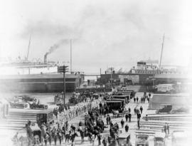 [View of a parade leaving the C.P.R. dock at the foot of Howe Street]