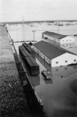 Flood waters surrounding buildings and train cars