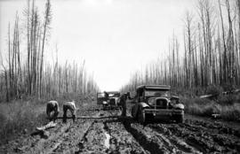 Automobiles in mud on the Monkman Pass Highway between Prince George and the Peace River district