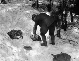 [A man collecting gear out of the snow]
