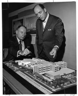E.J. Desjardins and Dr. A.C. Pinkerton point to architectural model of G.F. Strong Rehabilitation...