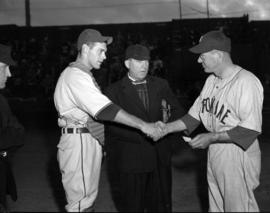 [Two baseball players, one from Spokane, shaking hands in front of an umpire]