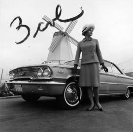 Woman posing next to 1964 P.N.E. program prize car