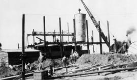 Tank being lifted into place by crane, construction site and workers