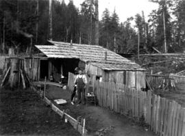 [Unidentified man with dog and cats in front of a shack]