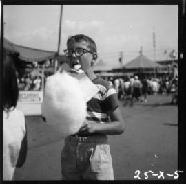 Boy eating cotton candy on P.N.E. grounds