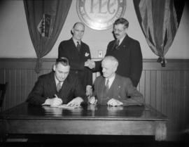 [Four men signing a deal in front of a Trades and Labour Council sign]