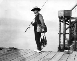 Mayor L.D. Taylor on pier with fishing pole and fish