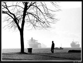 Man walking along path with four ships in the background