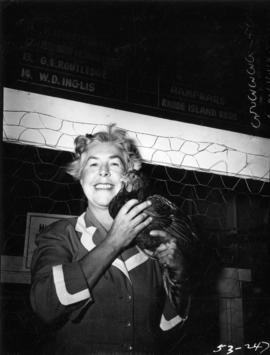 Woman posing with hen in Poultry building